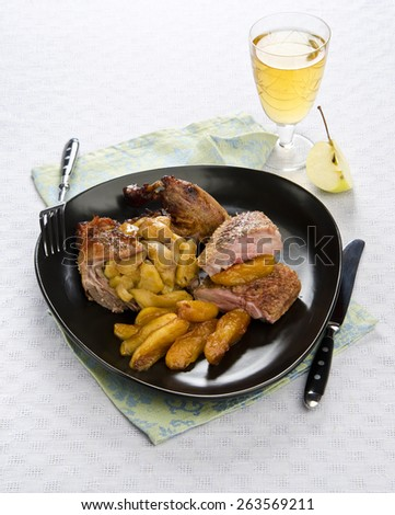 Roast duck with caramelized apples in wine on black dish blue tablecloth with a glass of white wine in the background - stock photo