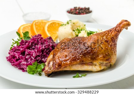 Roast duck with dumplings, red cabbage and oranges - stock photo