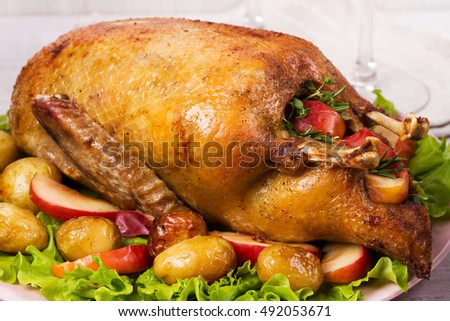 Roast duck with potato, apples, lettuce, thyme and rosemary. Stuffed festive duck