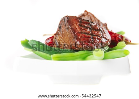 roast fillet mignon on a white ceramic plate with peppers - stock photo