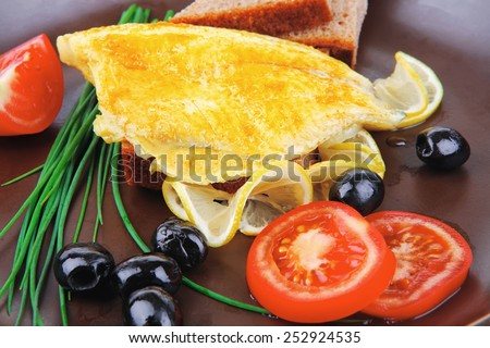 roast fish fillet with tomatoes,chives and bread on plate - stock photo