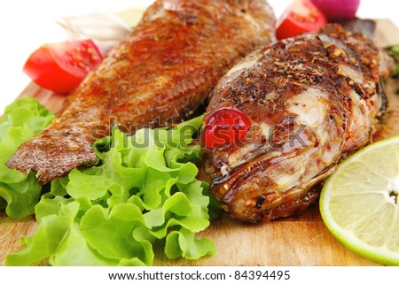 roast golden fish on wooden plate served with lemon and salad