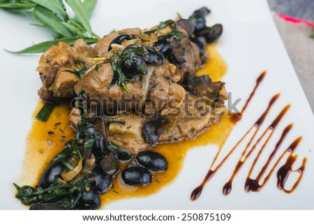 Roast lamb chops with black olives  on a plate on a wooden table in a restaurant
