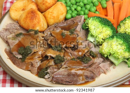 Roast lamb dinner with vegetables, gravy and mint sauce.