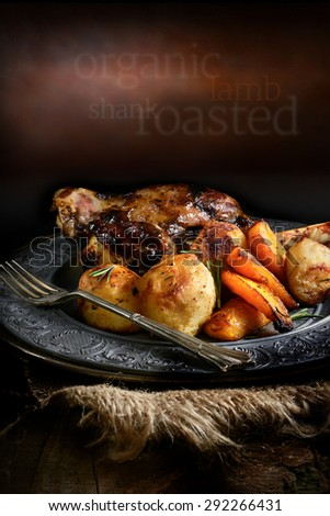 Roast lamb shank with roasted potatoes and carrots styled in a rustic setting with generous copy space. Concept image for home cooking or your bistro or restaurant menu cover design. - stock photo