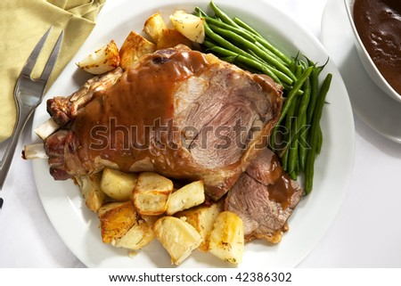 Roast leg of lamb on a serving platter, with potatoes, beans, and gravy. - stock photo