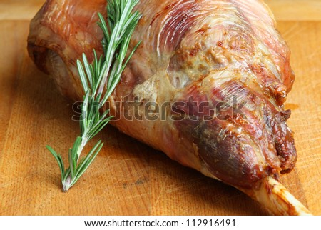 Roast leg of lamb, resting on carving board and  garnished with a sprig of rosemary. - stock photo