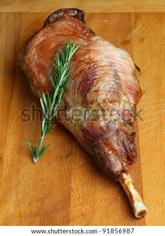 Roast leg of lamb resting on wooden carving board - stock photo