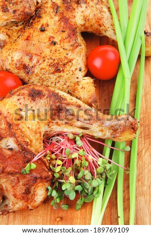 roast meat : chicken legs garnished with green sprouts and peppers on wooden plate isolated over white background - stock photo