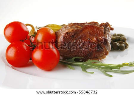 roast meat medallion with cherry tomatoes on white plate