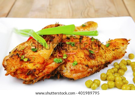 roast meat : roasted chicken legs garnished with green peas , peppers , and garlic on white plates over wooden table - stock photo