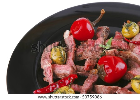 roast meat slices served on black dish over white