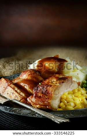 Roast pork bellies meal with creamed potatoes, seasonal vegetables and sage and onion stuffing in a creatively lit, rustic setting. Accommodation for copy space. - stock photo