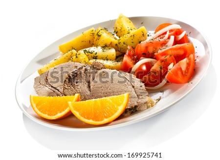 Roast pork, boiled potatoes and vegetable salad - stock photo