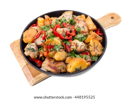 Roast pork fillets with potatoes and paprika. Isolated on a white background.