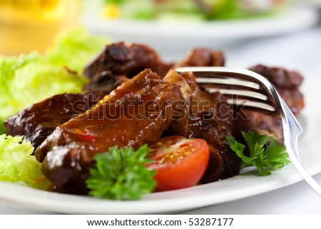 Roast pork ribs with herbs and vegetables - stock photo