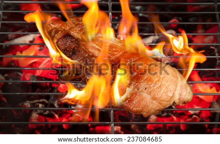 Roast pork with flames on the grill