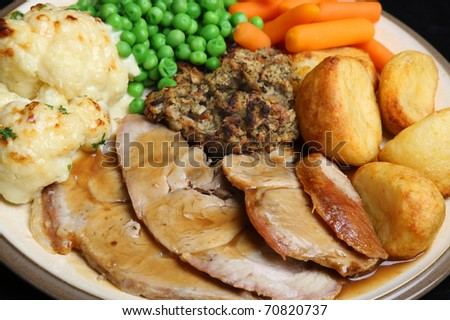 Roast pork with stuffing, roast potatoes, cauliflower cheese, peas, carrots and gravy. - stock photo