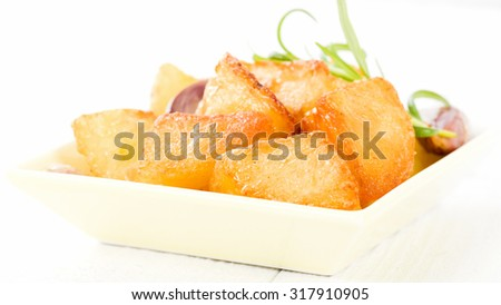 Roast Potatoes - White potatoes roasted with garlic and rosemary in goose fat on a white background. - stock photo
