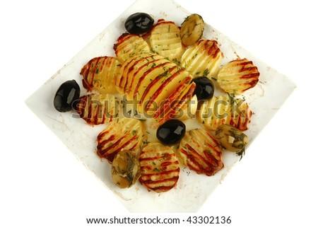 roast potatoes with black olives on white dish - stock photo