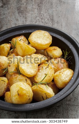 Roast Potatoes with rosemary and sea salt, in black serving dish. - stock photo