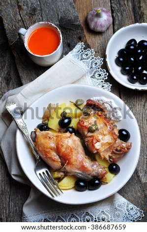 Roast rabbit in white wine with rosemary, olives and capers - stock photo