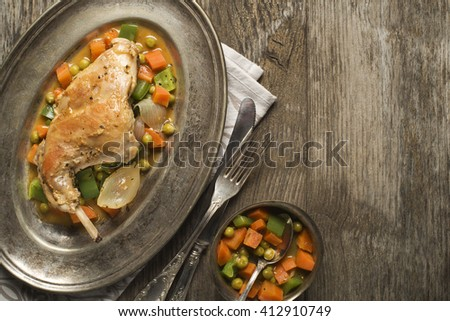 Roast rabbit leg with stewed vegetables on wooden table.