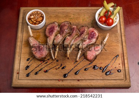 Roast rack of lamb served on wooden board - stock photo