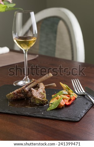Roast rack of lamb served with pepper, corn and glass of white wine on wooden table at restaurant - stock photo