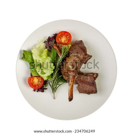 Roast rack of lamb with vegetables on plate isolated on white background - stock photo