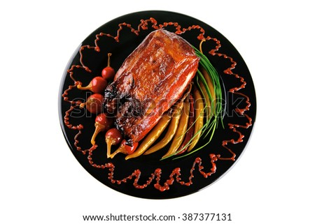 roast red beef meat bbq bloc served on black plate  with green chives adn red hot pepper on black plate isolated over white background - stock photo