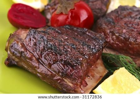 roast rib's on green dish  with snakes - stock photo