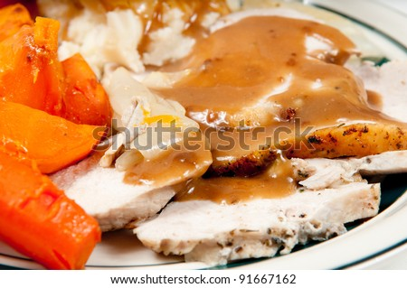 roast turkey breast with mashed potatoes, sweet potatoes, carrots and lots of gravy - stock photo