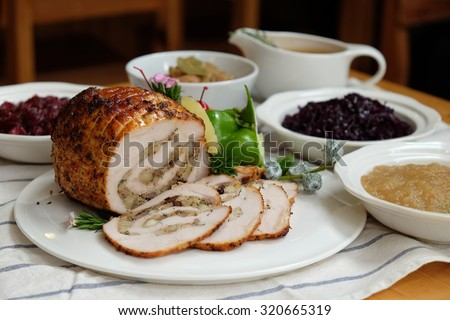 Roast Turkey Breast with Stuffing, Gravy, Apple Sauce, Braised Red Cabbage, Cranberry Sauce on a table, Selective focus - From above - stock photo