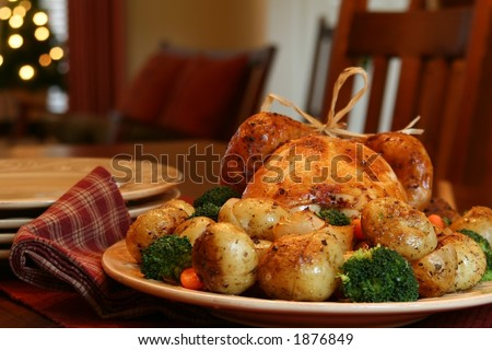 Roast turkey, potatoes, onions, broccoli and carrots, Christmas tree in background. - stock photo