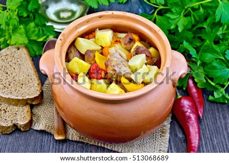 Roast with chicken, potatoes, squash and sweet peppers in a clay pot on a napkin of burlap, bread and parsley on a wooden board background