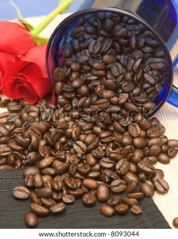 roasted and imported coffee beans spilling out of blue glass coffee cup set against different colors of tablecloths and two red roses as accent pieces - stock photo