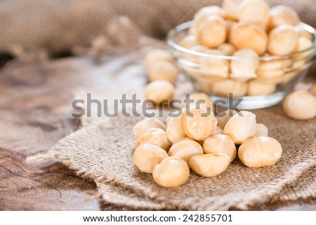 Roasted and salted Macadamia nuts on rustic wooden background - stock photo
