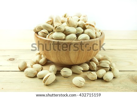 Roasted and salted pistachios in shell on wooden cup on wooden table on white background - stock photo