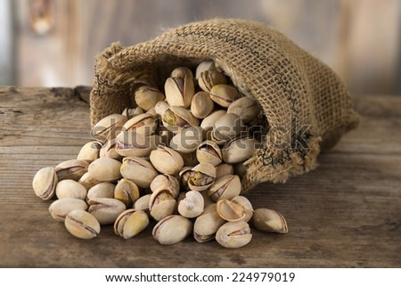roasted and salted pistachios pour out of a burlap bag - stock photo