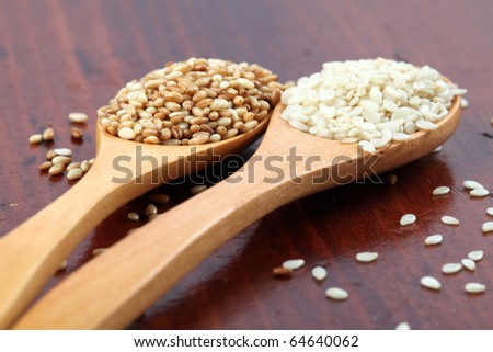 Roasted and white sesame seeds on wooden spoons
