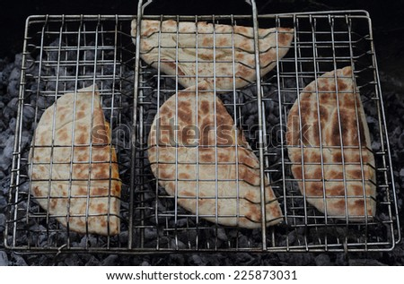 Roasted arabic bread pita on the grill photo - stock photo