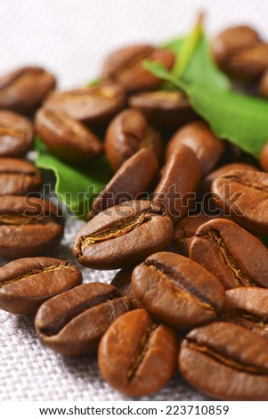 roasted arabica coffee beans with fresh green leaves, scattered on the table - stock photo