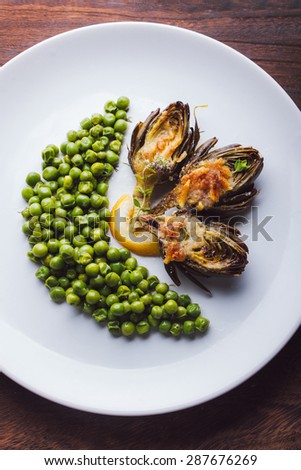 Roasted artichokes with young peas, served in a white dish on a wooden table - stock photo