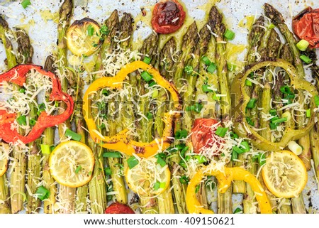 Roasted asparagus spears with lemon slices, cherry tomatoes, bell pepper rings and vegan parmesan cheese. - stock photo