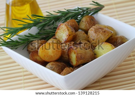 Roasted baby potatoes with fresh rosemary, close up  - stock photo