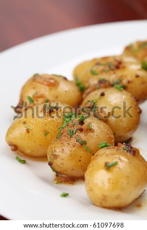 Roasted baby potatoes with onion, mustard seed and chives - stock photo