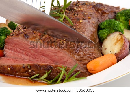 Roasted beef loin tri-tip, garnished with vegetables - stock photo
