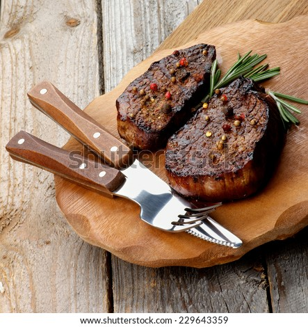 Roasted Beef Steaks with Spices and Rosemary on Wooden Plate with Fork and Table Knife on Rustic Wooden background - stock photo