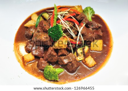 Roasted beef with red wine sauce on white dish - stock photo